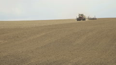 A tractor sows plowed field using a seeder Stock Footage