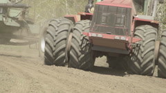 A tractor with a hitched sowing machine, rides on field closeup Stock Footage