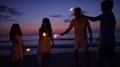 Silhouette of Latin American family at sunset with fun sparklers on the beach Stock Footage