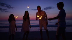 Spanish parents and kids enjoying party with sparklers on the beach at sunset Stock Footage