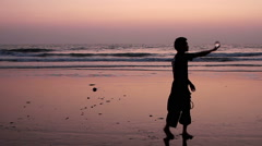 Unidentified man juggling with glass ball on the beach Stock Footage
