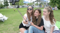 Three girls taking selfie photo in park with a mobile phone and a selfie stick Stock Footage