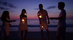 Spanish family celebrating a birthday with sparklers on the beach at sunset Stock Footage