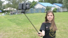 Brunett girl taking selfie photo in park with a mobile phone and a selfie stick Stock Footage