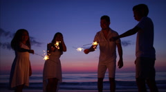 Silhouette of Spanish family partying on the beach with sparklers at sunset Stock Footage