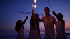 Hispanic family celebrating a birthday with sparklers on the beach at sunset Stock Footage