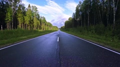 Empty asphalt road with traffic lanes in dense coniferous forest Stock Footage