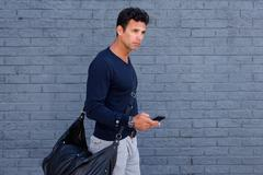 Male traveler walking with mobile phone and bag - stock photo