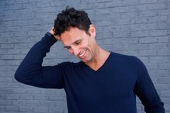 Handsome man laughing with hand in hair against gray wall Stock Photos