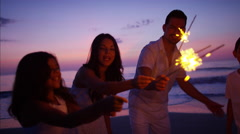 Latin American family having fun at sunset with sparklers on the beach Stock Footage