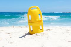 Life buoy in sand at beach - stock photo