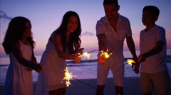Silhouette of Spanish family at sunset with fun sparklers on the beach Stock Footage