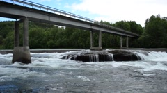 massive concrete bridge raging over massive flooded river torrent in summer - stock footage