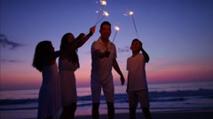 Hispanic family having fun at sunset with sparklers on the beach by the ocean Stock Footage