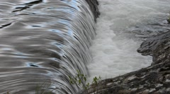 Clean fast flowing river water flowing over small concrete barrier waterfall Stock Footage