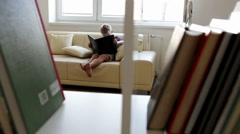 Boy sits on the sofa at home and reads some magical book with interest - stock footage