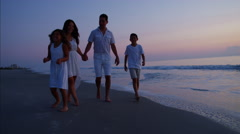 Happy Spanish family enjoying their vacation together on the beach at sunrise Stock Footage
