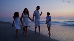 Attractive Latin American family walking on the beach by the ocean at sunset Stock Footage