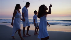 Happy Hispanic family enjoying their holiday together on the beach at sunset Stock Footage