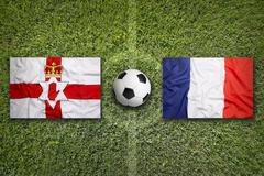 Northern Ireland vs. France flags on soccer field - stock photo