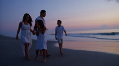 Attractive Latin American family walking on the beach by the ocean at sunrise Stock Footage
