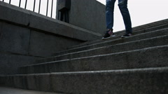 Close up of a female legs in blue jeans and black sneakers running down stairs Stock Footage