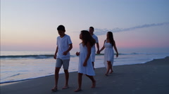 Carefree Hispanic family walking together on the beach at sunset Stock Footage