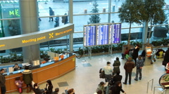 People near information board inside arrival hall in international airport Stock Footage