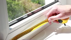 Man measuring a window with yellow tape-line Stock Footage