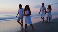 Attractive Spanish family walking on the beach by the ocean at sunrise Stock Footage