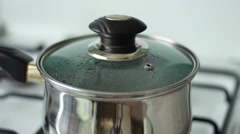 Boiling water in a steel pan under the cover Stock Footage
