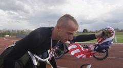 4K Winning disabled athlete at racing event doing victory lap with American flag Stock Footage