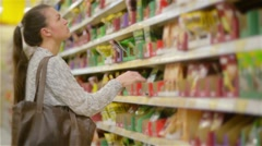 Young woman choosing spices in grocery store, beautiful woman shopping in a Stock Footage