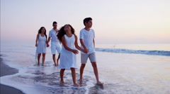 Carefree Spanish children enjoying time with parents on beach at sunrise Stock Footage