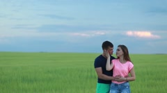 Adorable young couple embracing and kissing tenderly in countryside at sunset Stock Footage