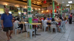 People eat noodles and other dishes inside a food court - stock footage
