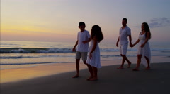 Silhouette of Latin American family walking together on the beach at sunset Stock Footage