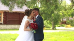 Beautiful happy young bride kissing handsome groom in sunlit park. Wedding Stock Footage