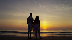 Silhouette of young Latin American couple enjoying sunrise together on the beach Stock Footage