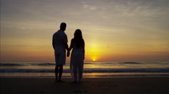 Silhouette of young Spanish couple enjoying sunrise on the beach Stock Footage