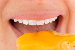 Extreame close up shot of a woman eating nacho cheees covered chips in shade Stock Photos
