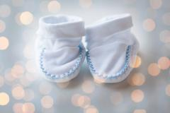 Close up of white baby bootees for newborn boy Stock Photos