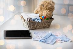 close up of baby clothes, toys and tablet pc - stock photo