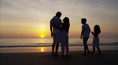 Silhouette of Latin American family on their beach holiday at sunrise Stock Footage