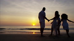 Sunset silhouette of Spanish family enjoying the sunset on the beach Stock Footage