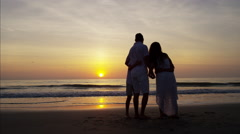 Silhouette of Hispanic family spending time together on the beach at sunset Arkistovideo
