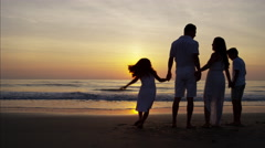 Silhouette of Latin American family on their beach vacation at sunrise Stock Footage