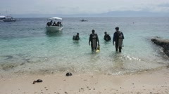 Scuba divers enter the water off the beach in the Philippines Stock Footage
