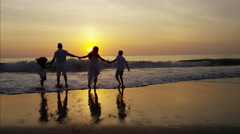 Silhouette of Hispanic family playing in the shallows on the beach at sunset Stock Footage