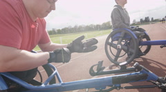 4K Disabled wheelchair athletics team prepare for training session at race track Stock Footage